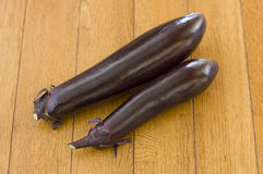 Two eggplant on wooden floor. Made with home garden vegetables Royalty Free Stock Photography