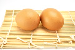 Two eggs on bamboo mat Stock Photo