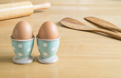 Two eggs in blue polka dot egg cups and baking utensils Royalty Free Stock Photography