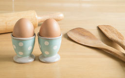 Two eggs in blue polka dot egg cups and baking utensils Royalty Free Stock Image