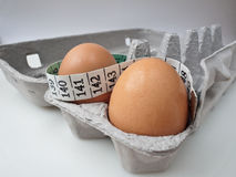 Two Eggs in Carton with Measuring Tape 2 Royalty Free Stock Images