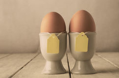 Two Eggs in Eggcups with Labels on String  Retro. A pair of brown eggs in eggcups with price tag style labels on string.  Old white wooden planked table.  Hues Stock Images