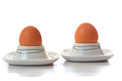 Two eggs in eggcups reflecting. On light background Stock Photo