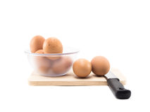 Two eggs and eggs in cup and knife on wood square isolated Stock Photography
