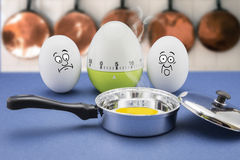 Two eggs with frightened face look at a frying pan Stock Photo
