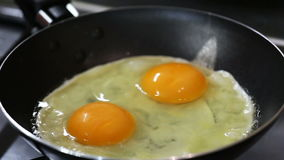 Two eggs are frying on a hot frying pan stock video footage