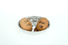 Two eggs with funny faces on oval foil tray, isolated on white background Royalty Free Stock Images