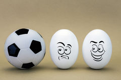 Two eggs look with strange face to a balloon of football Stock Photo