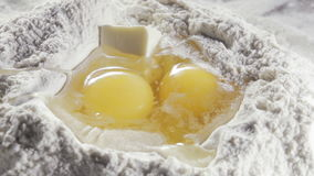 Two eggs in the middle of bleached wheat flour stock video footage