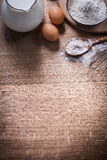 Two eggs pitcher milk bowl and sppon with flour Royalty Free Stock Photos