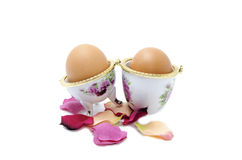 Two eggs in porcelain with artificial petals Royalty Free Stock Photo