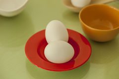 Two Eggs in a red plate isolated on glass background Stock Photos