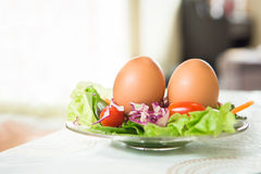 Two eggs on the salad dish Royalty Free Stock Images