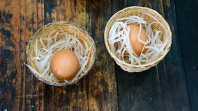 Two eggs in small baskets royalty free stock images