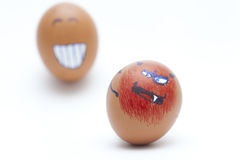 Two eggs smiley and angry face Stock Photos