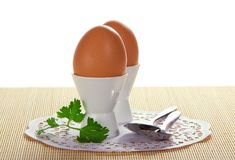 Two eggs, spoons and parsley on the cloth Royalty Free Stock Images