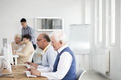 Elder men using computers. Two elder men using computers to test their knowledge of theory from lectures stock photos