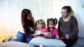 Older women and baby girls four communicate and busy with own affairs, sitting on floor on background of wall with. Two elder sister girls together with little stock footage