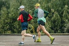 Two elderly athlete run along river stock photo
