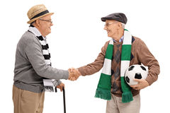 Two elderly football fans shaking hands Stock Image