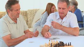 Two elderly friends playing cards stock footage