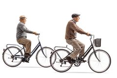 Two elderly gentlemen riding bicycles. Isolated on white background royalty free stock images
