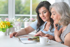 Two elderly girlfriends are reading a magazine. At the table stock image