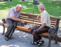 Two elderly grandfather playing on a park bench in chess. In Lviv stock photos