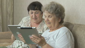 Two elderly grandmothers holding digital tablets. Two elderly grandmothers sitting on a beige couch at home. Each grandmother holds the silver digital tablet stock video