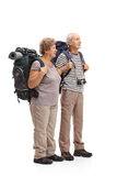 Two elderly hikers looking in the distance. Full length profile shot of two elderly hikers looking in the distance isolated on white background Royalty Free Stock Photo