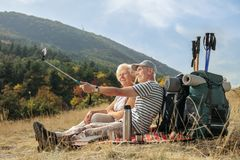 Two elderly hikers seated on a blanket taking a selfie. With a stick outdoors Stock Images