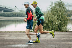 Two elderly joggers run along embankment of river Royalty Free Stock Photos