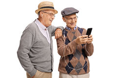 Two elderly men listening to music on a phone Stock Photo