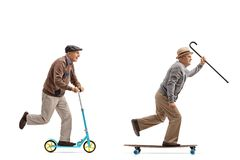 Two elderly men with one of them riding a scooter and the other Stock Photos