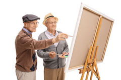 Two elderly men painting on a canvas Royalty Free Stock Photos