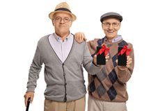 Two elderly men with phones wrapped with red ribbons as presents Royalty Free Stock Photos