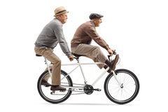 Two elderly men riding a tandem bicycle with legs up. Full length shot of two elderly men riding a tandem bicycle with legs up isolated on white background royalty free stock photography