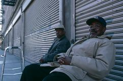 Two elderly men sat outside of closed shops, Manhattan, New York, USA Royalty Free Stock Image