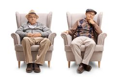Two elderly men seated in armchairs Royalty Free Stock Images