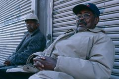 Two elderly men sitting in front of a closed shop, Manhattan Royalty Free Stock Photography