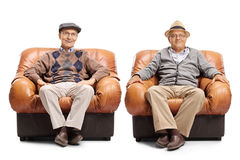 Two elderly men sitting in leather armchairs Royalty Free Stock Images