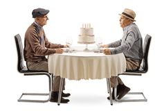 Two elderly men at a table blowing candles on a cake. Isolated on white background stock photography