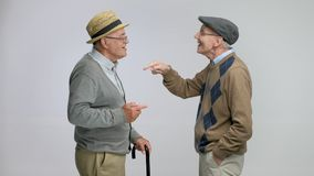 Two elderly men talking and high fiving each other. Isolated on gray background stock footage