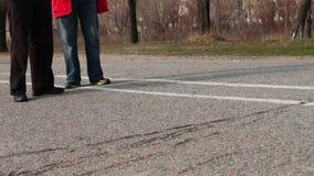 Two elderly men talking and walking down the street.walking feet on pavement. stock video