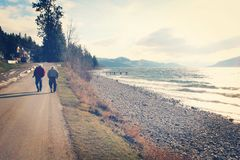 Two elderly men walking alongside of rocky beach. Two elderly men walking along paved trail next to rocky beach and rolling waves along lake shore. Pier, lake royalty free stock image