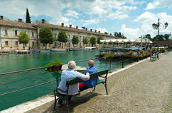 Two elderly people. Two elderly men enjoying the view in the picturesque harbor of peschiera del garda Royalty Free Stock Photo