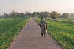Two elderly people return from the evening walk stock photography
