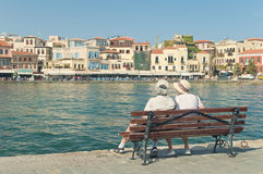Two elderly people sitting on bench looking at city view Stock Images