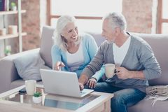 Two elderly people are sitting at home at the weekend, drinking stock images