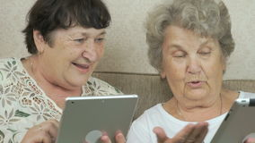 Two elderly sisters holding silver digital tablets. Two elderly sisters sitting on a beige sofa at home. Each woman holds the silver digital tablet stock video footage